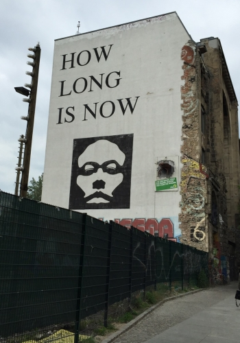 large text mural reads How Long Is Now - Berlin