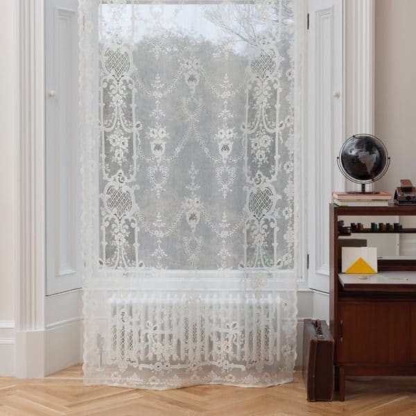 Ayrshire Lace Panel - Highland Rose Design. Lifestyle image showing panel hanging in a traditional window.