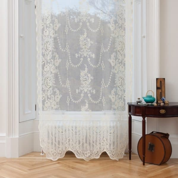 Ayrshire Lace Window Panel in Iona design. Lifestyle image of the Iona panel hanging in a traditional window.