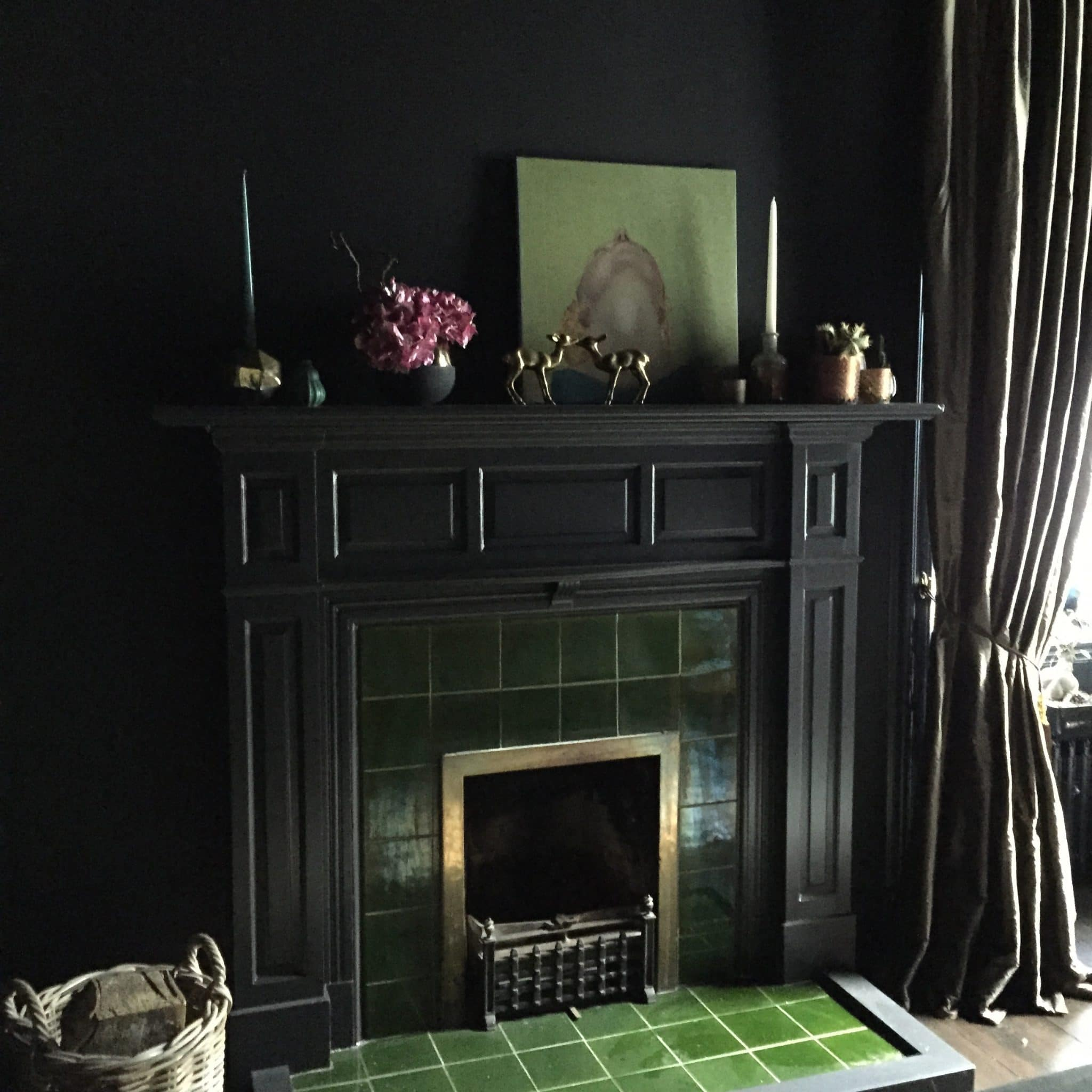 dining room painted dramatic black with green tiled fireplace