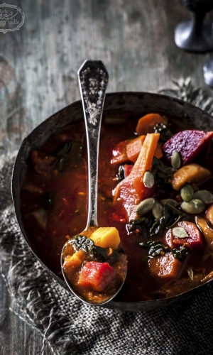 colourful vegetable stew in antique metal bowl with old steel spoon