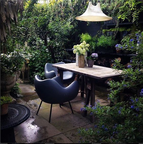 modern designer chairs in a leafy garden with mouth blown glass light