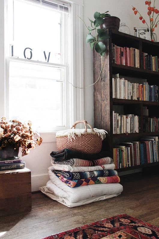 modern rustic room with pile of blankets, woven basket and bookcase