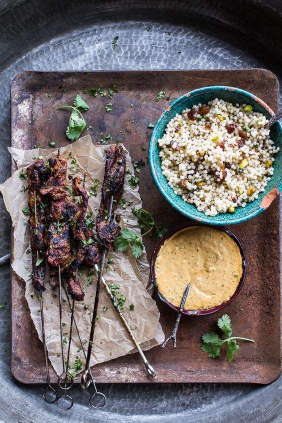 rustic lamb kebabs on tray with tabouleh and dips