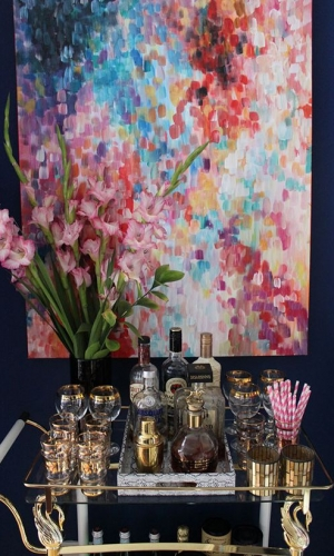 Bar trolley with bottles and flowers and colourful artwork behind