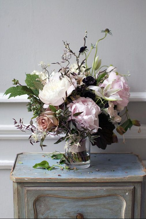 vase of romantic wild flowers and roses on a table