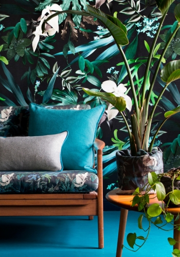 blue and green botanical wallpaper and sofa with plants