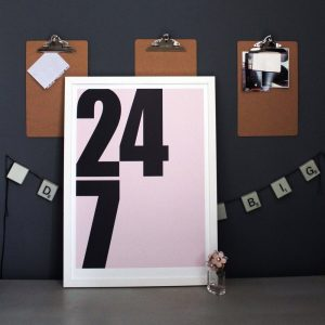 24 7 art print by we are amused with numbers on a pink backgorund in frame against a dark grey wall with office clipboards 30 x 40