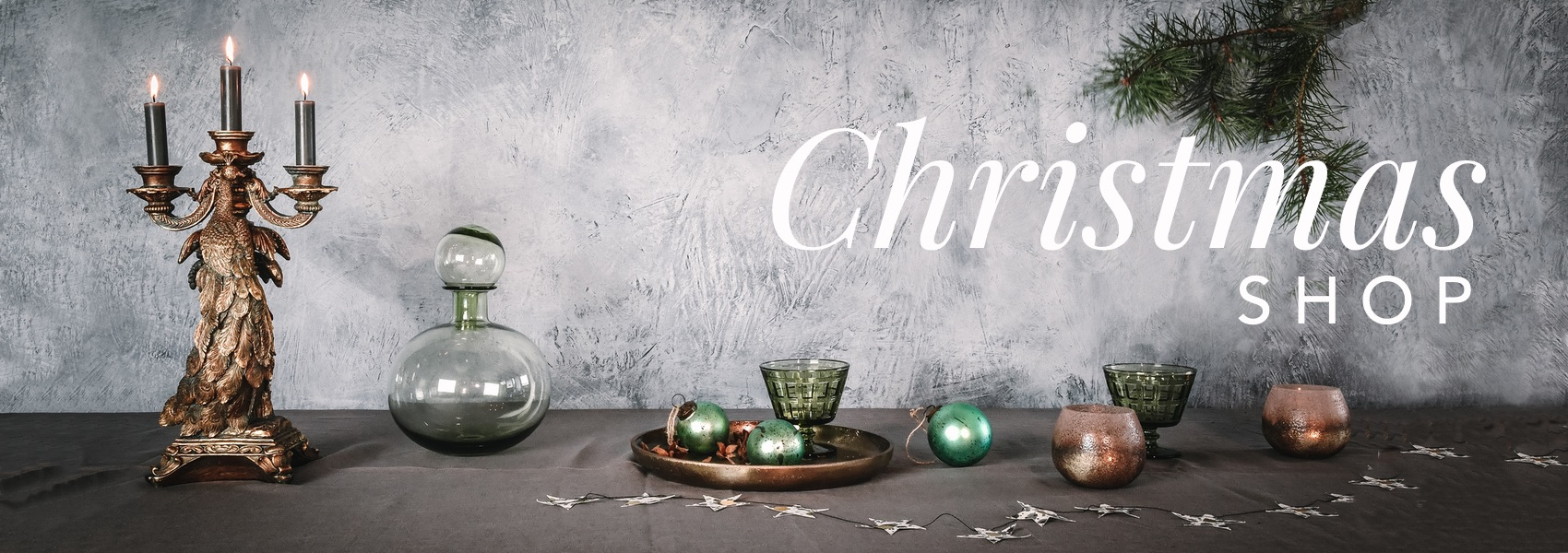 Curious Egg Christmas Shop 2019.  Selection of quirky and unusual Christmas decoration items displayed on a table with a pine branch in the background.