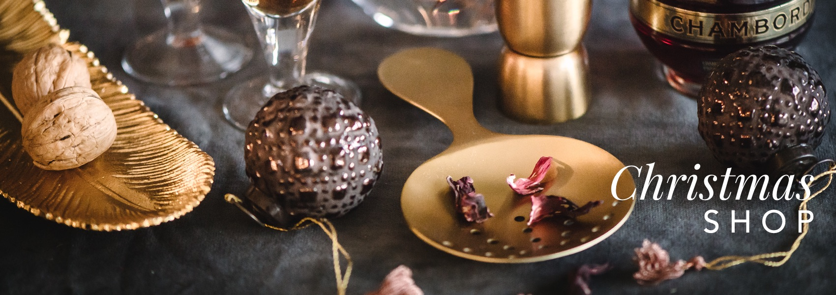 Curious Egg Christmas Shop 2018.  Assorted gold, bronze and copper Christmas decorations and decorative accessories with Chambord champagne cocktails and petals.