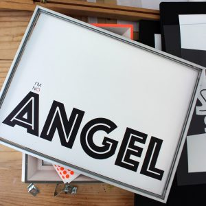 I'm no Angel art print by we are amused laid flat on top of a frame with orange trim on a desk 30 x 40