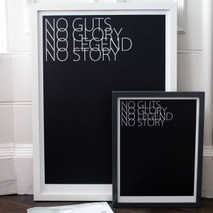 No Guts No Glory art print by We are amused in large white frame and one in smaller black frame stacked against a wall lifestyle shot