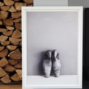 Shoe Lasts art print by We are Amused in a white frame leaning against a wall with a stack on wooden logs behind on the left 30 x 40