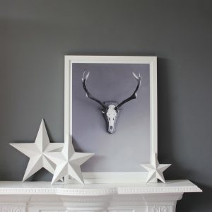 Stag art print by we are amused in white frame on mantle piece against grey wall with white decorative stars plaaced in front of frame 30 x 40