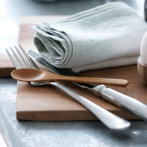 Bamboo spoon resting on other cutlerynext to a linen napkin