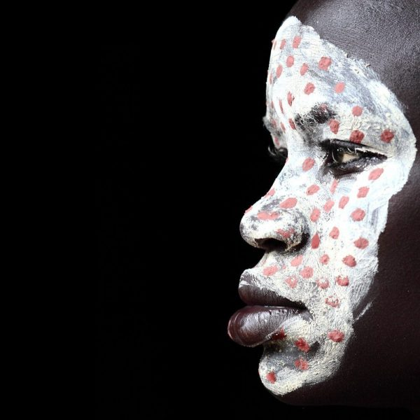 Suri tribe girl with decorated face of painted dots.  Photo by Mario Gerth for sale at curiousegg.com