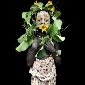 Suri tribe girl with flowers.  Photo by Mario Gerth for sale at curiousegg.com