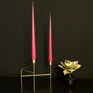 raspberry taper candles in gold candleholder
