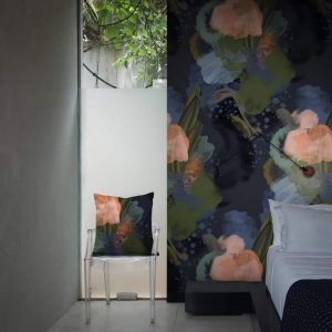 English Rose Wallpaper in Midnight Colour by Feathr at Curious Egg.  Lifestyle image with a bed in the foreground and a chair with matching cushion.