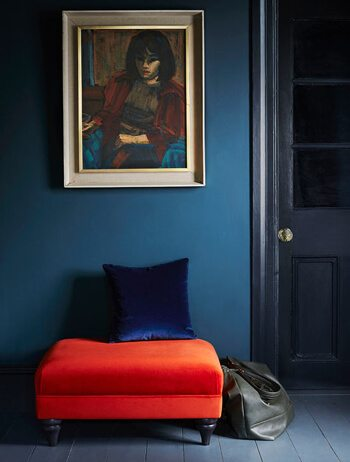A hallway with dark blue walls and burnt orange seat with expressionist painting above