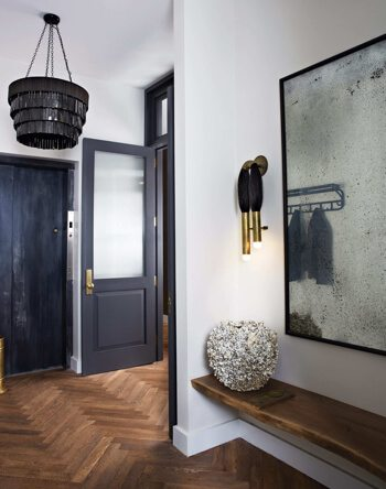 Hallway with dark blue and white walls and parquet flooring with modern designer lighting and artisan ceramic and mirror