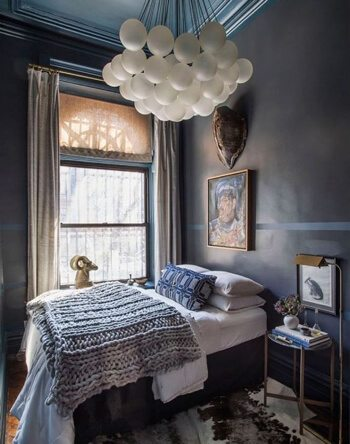 Small dark blue bedroom with lighting by apparatus studio and welsh blankets and expressions paintings