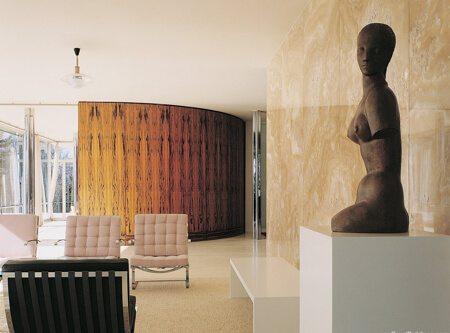 An interior design by Ludwig Mies Van Der Rohe  with modern sculpture and pink seats