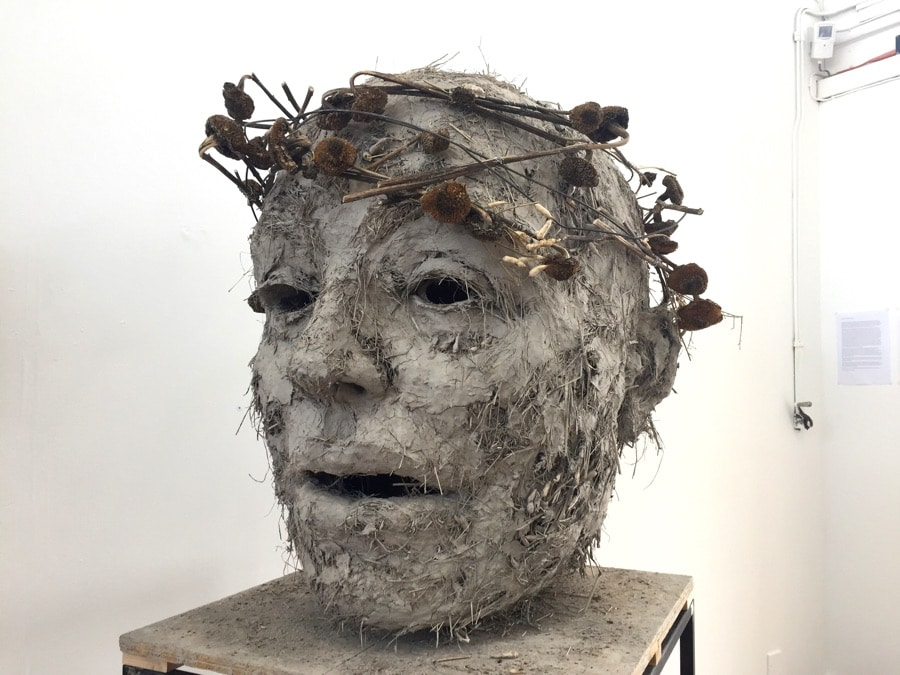 giant sculpture of a head made of clay and straw