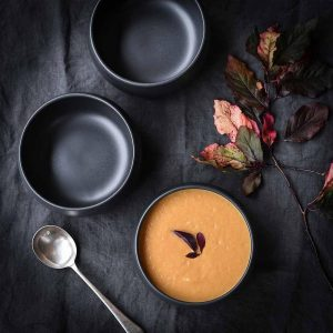 Cueva black ceramic bowl lifestyle image with pumpkin soup