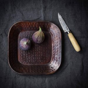little bronze hammered tray with figs and a small fruit knife