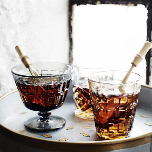 Art Deco style cocktail glasses with a bamboo whisk inside one of them on a tray beside the window