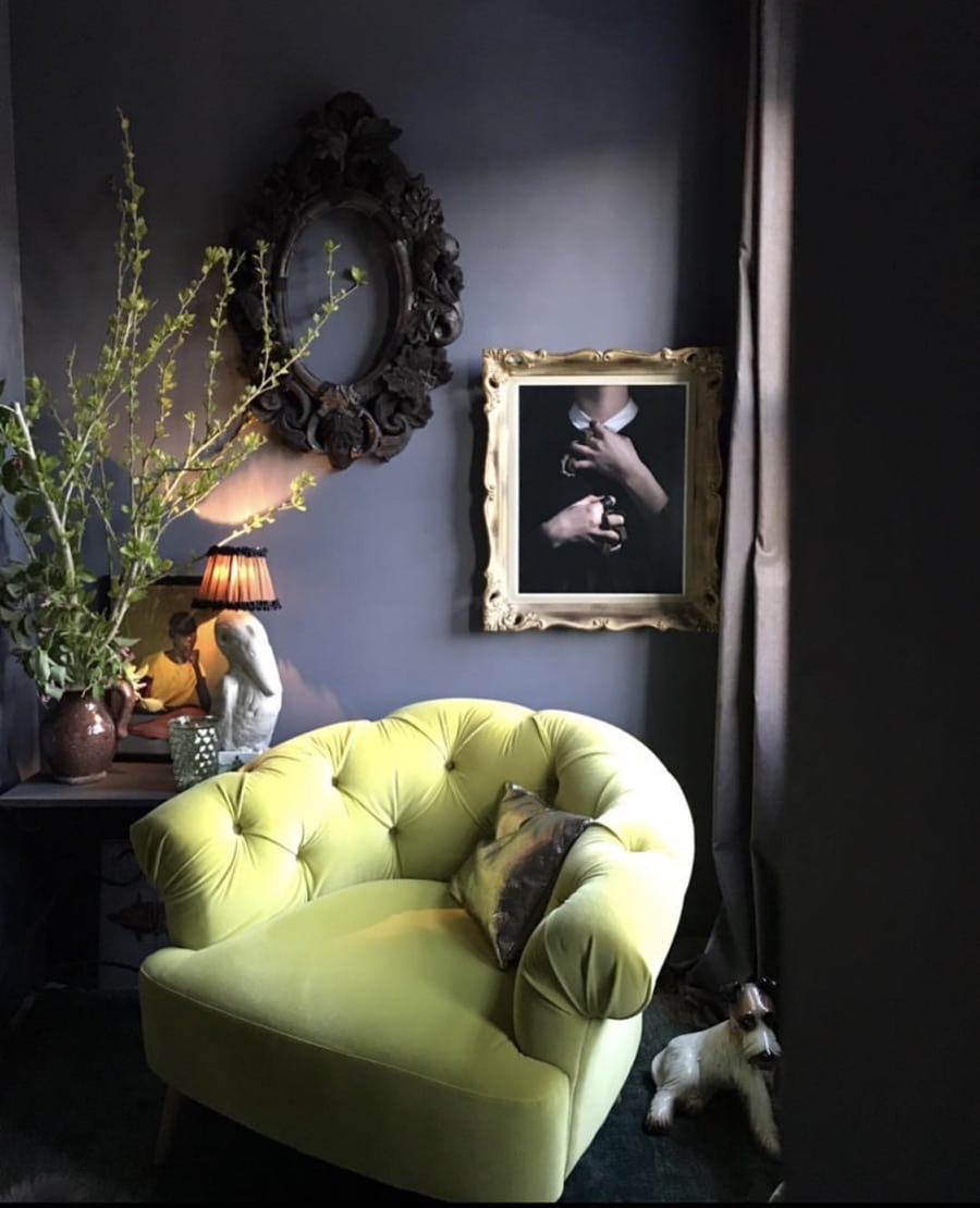 green velvet chair next to draw grey wall and artworks