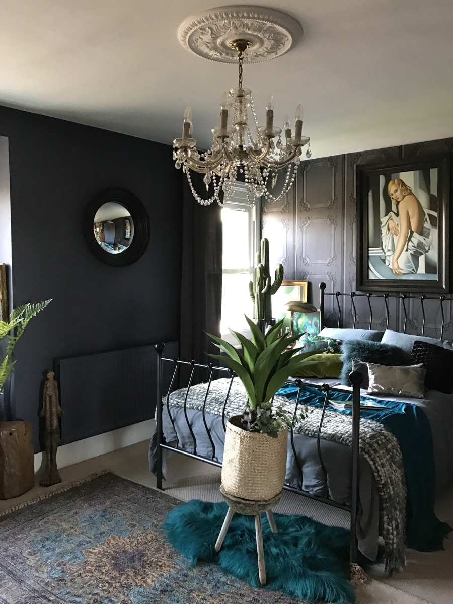 bedroom with dark grey walls and colourful throws