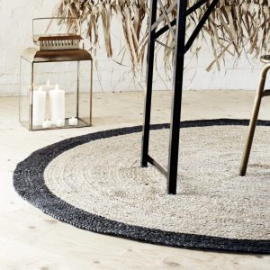 detail of round rattan rug with black band under a contemporary style table