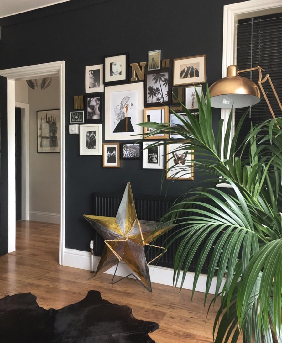 living room with dark wall and gallery wall art with gold star decorations