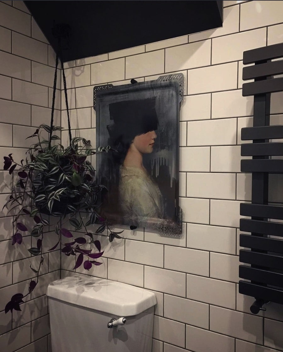 bathroom with white tiles and artwork next to a hanging plant