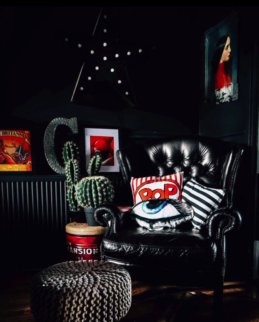 Black living room with bold home accessories and dyed black leather chair