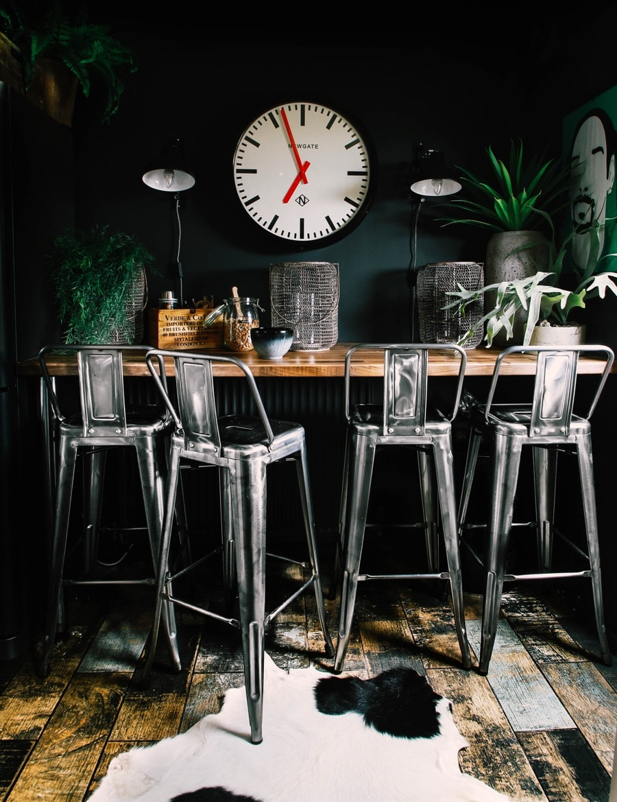 breakfast bar with bar stools and black wall with wall clock