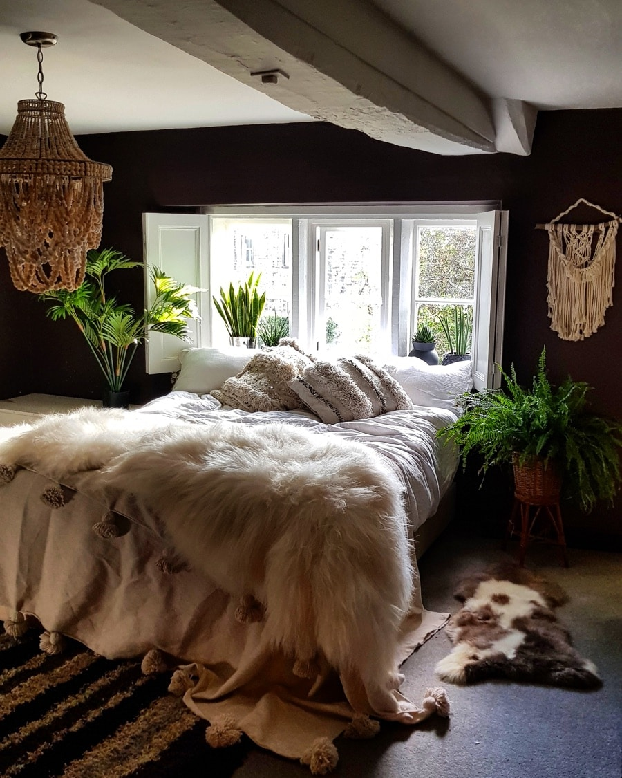 a bedroom with boho macrame wall hanging and beaded light