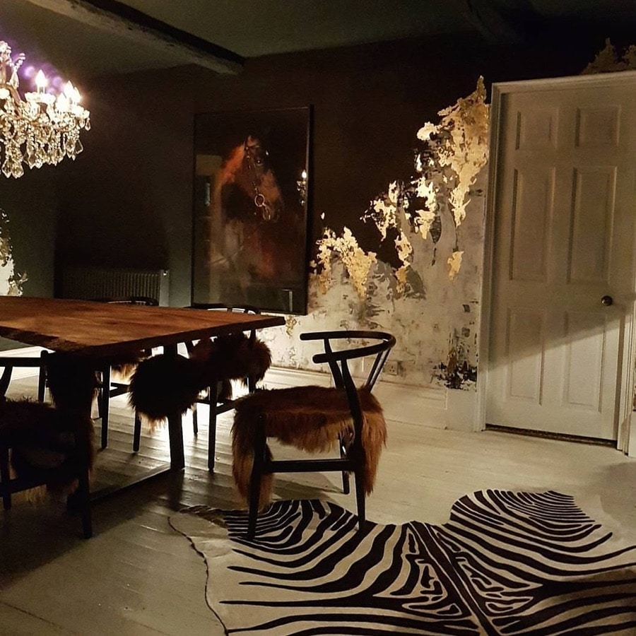 a dramatic dining room with distressed wall finish and gold leaf detailing