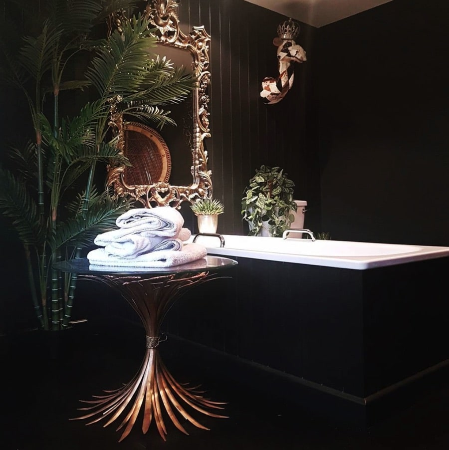 a black bathroom with gold details