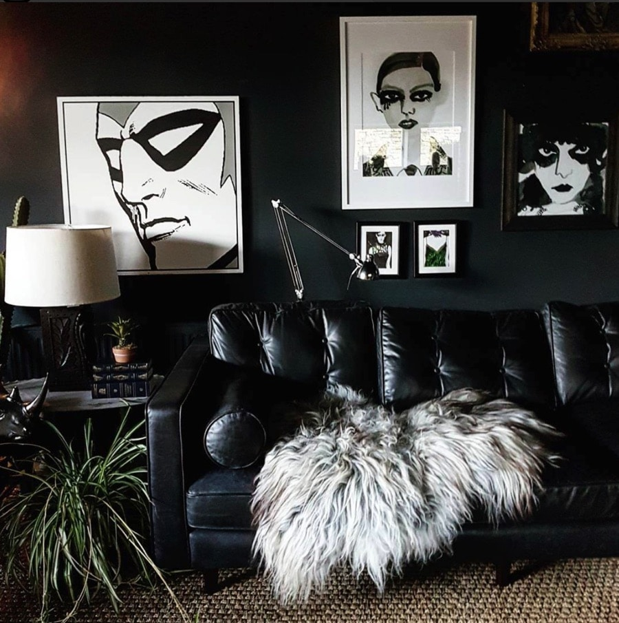 black walls in a living room with black leather sofa and monochrome artworks
