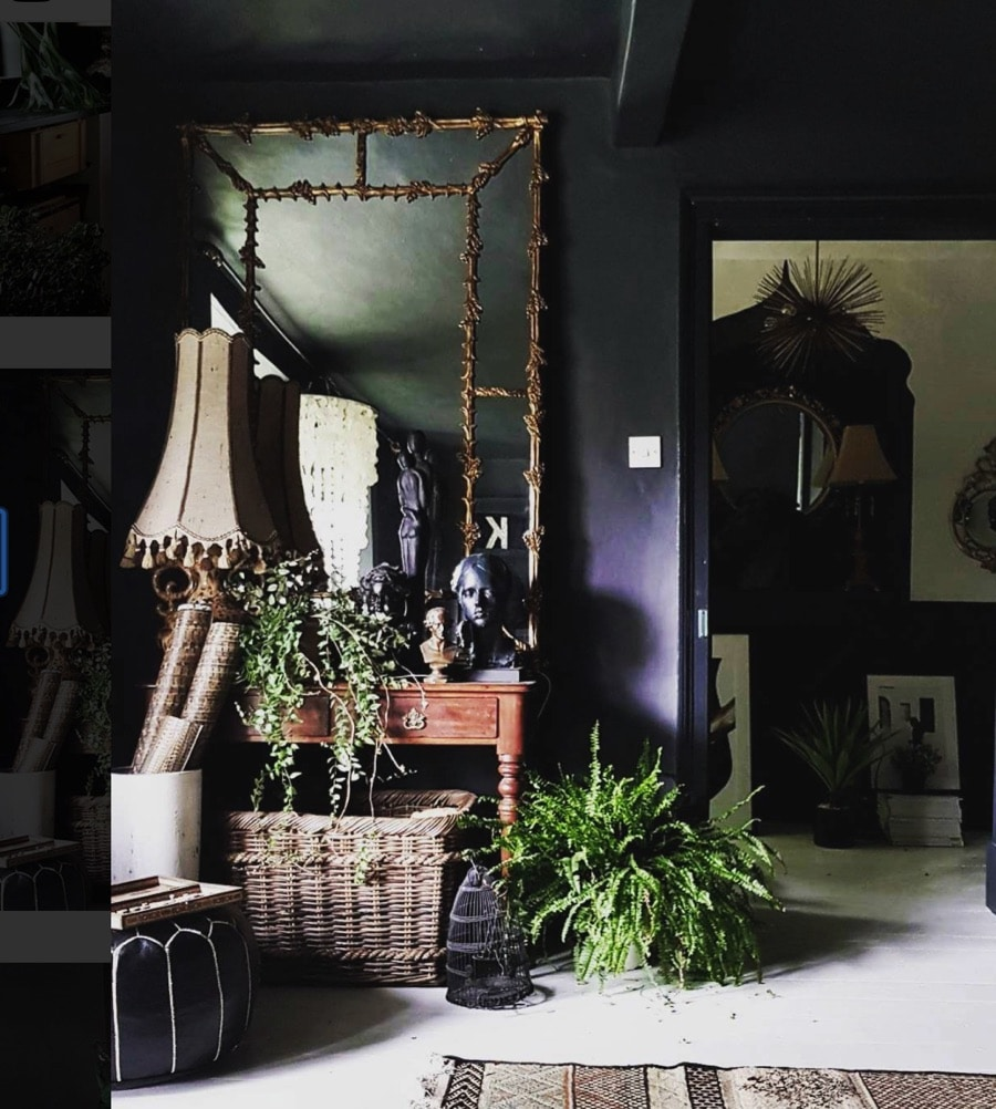 Dark walls and a console table with lamp and sculptures