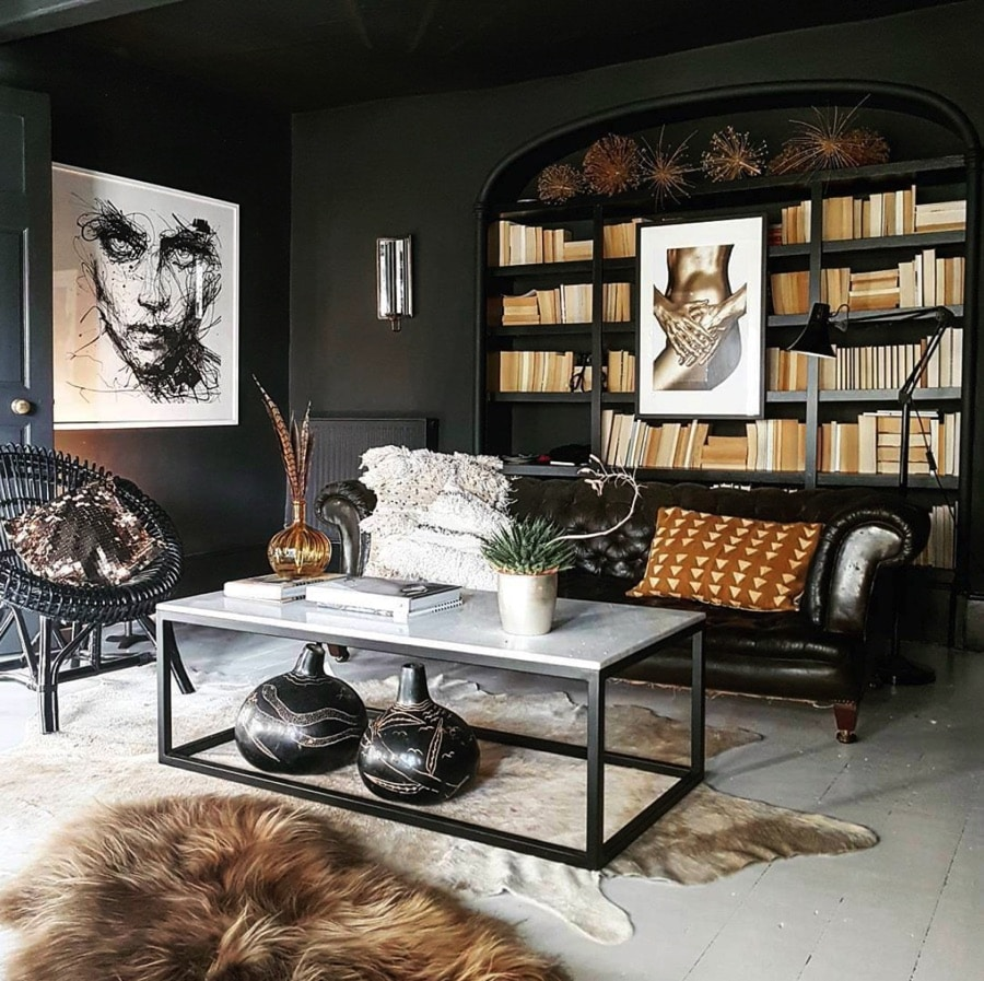 Ricing room with dark walls and art with a library