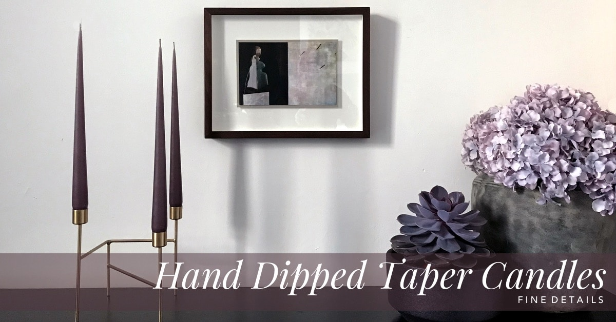 Curious Egg. Danish Hand Dipped Taper Candles. Lifestyle Image with 3 Candles in French Lavender on a Gold Strand candle stand with a picture in the background and vases with flowers.
