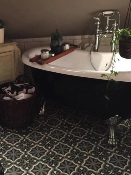 patterned tiles in bathroom with claw foot bath