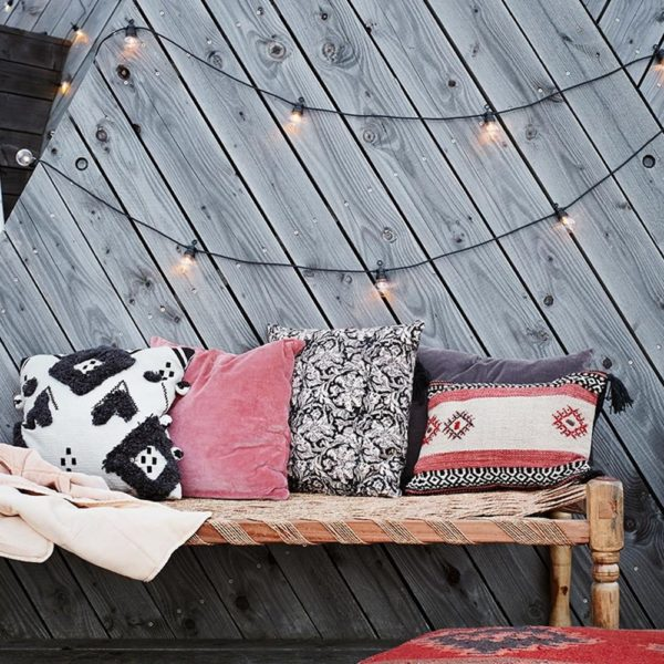 Led indoor and outdoor party lights on black cord.  Lifestyle image with wooden decking background and bench with coloured woven cushions in the foreground.