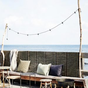 Led indoor and outdoor party lights on black cord.  Lifestyle image with lights hung between two branches in a beach bar with the sea in the background.