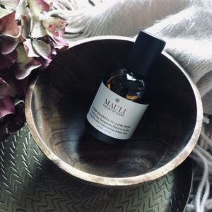 Mauli Dharma sleep pillow mist lifestyle image with wooden bowl and petals.