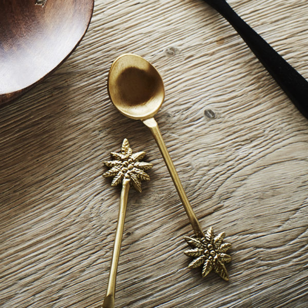 Brass teasoon with palm tree motif on wooden table